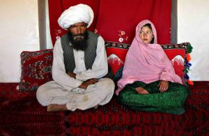 Faiz Mohammed, 40, and Ghulam Haider, 11, sit in her home prior to their wedding in the rural Damarda Village, Afghnanistan on Sept. 11, 2005. Ghulam said she is sad to be getting engaged as she wanted to be a teacher. Her favorite class was Dari, the local language, before she was made to drop out of school. Married girls are seldom found in school, limiting their economic and social opportunities. Parents sometimes remove their daughters from school to protect them from the possibility of sexual activity outside of wedlock. It is hard to say exactly how many young marriages take place, but according to the Afghan women's ministry and women's NGOs, approximately 57 percent of Afghan girls get married before the legal age of 16. In addition, once the girl's father has agreed to the engagement, she is pulled out of school immediately. Early pregnancies also result in an increase in complications during child birth.
